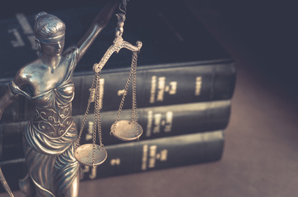 Lady justice statue holding scales with law books in background
