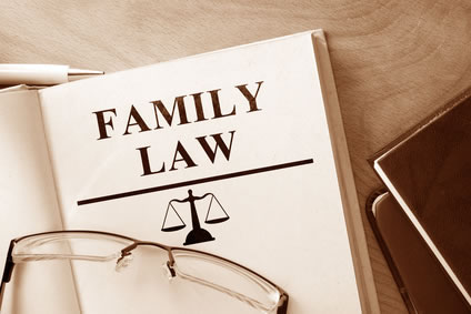 Family law book with pen, eyeglasses, and other books nearby